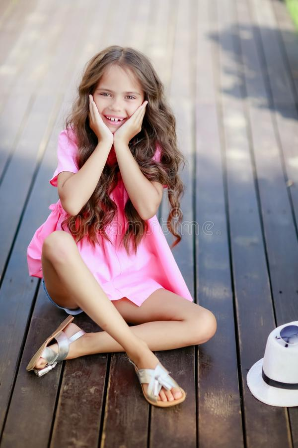 Fashion little girl model wearing a pink checkered shirt, hat and sunglasses in city royalty free stock image