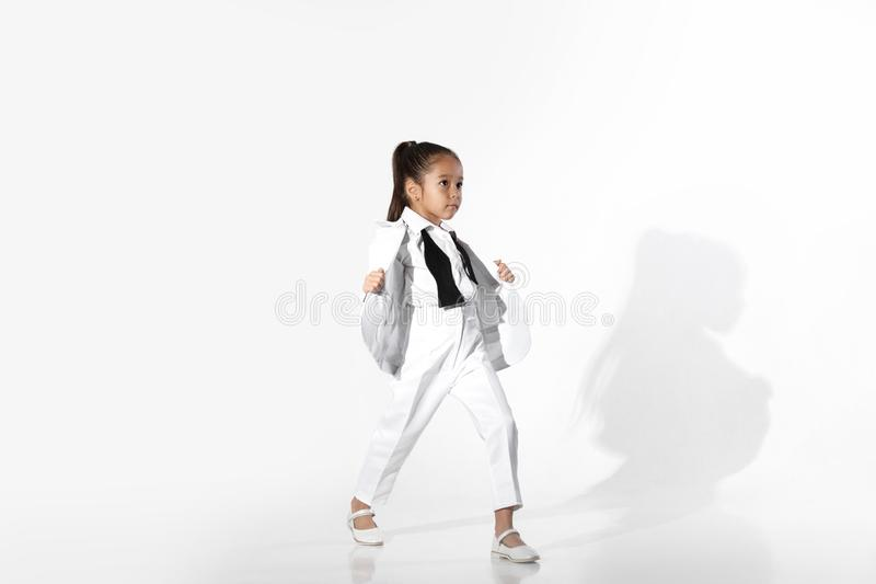 Fashion little girl model in a white suit and bow tie royalty free stock image