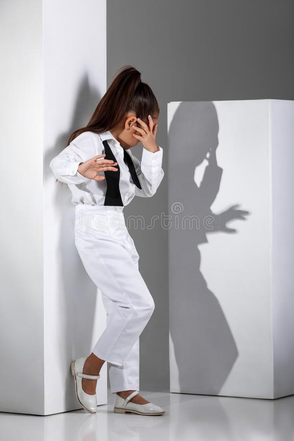Fashion little girl model in a white suit and bow tie stock photo