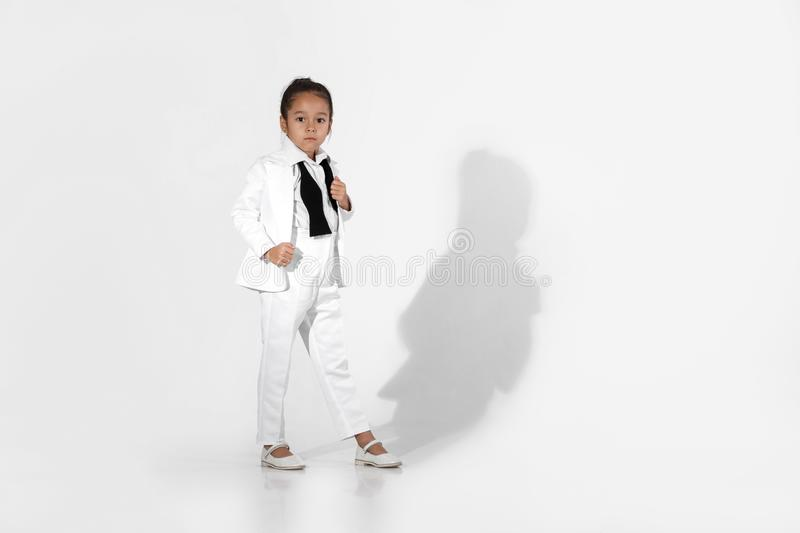Fashion little girl model in a white suit and bow tie royalty free stock photo