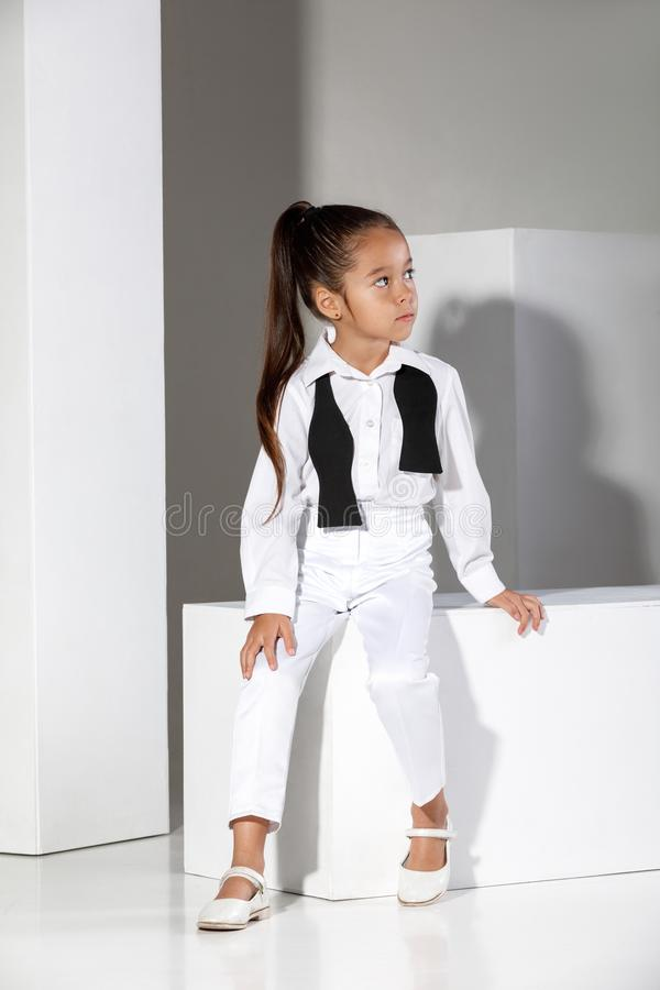 Fashion little girl model in a white suit and bow tie royalty free stock images