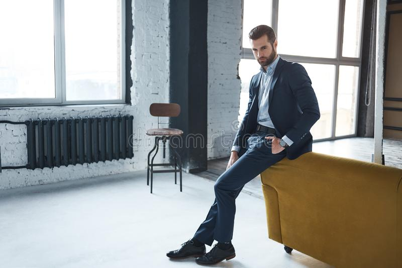 Fashion look. Attractive and stylish businessman is thinking about work in the modern office royalty free stock photos