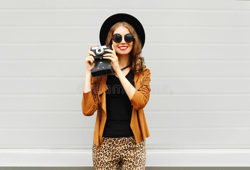 Fashion look, pretty cool young woman model with retro film camera wearing a elegant hat, brown jacket outdoors in city stock photo