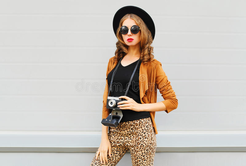 Fashion look, pretty cool young woman model with retro film camera wearing elegant hat, brown jacket posing outdoors royalty free stock photography