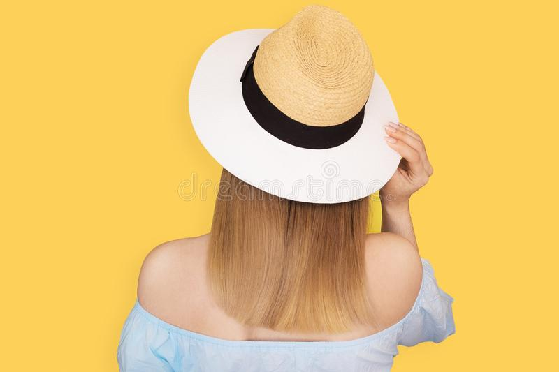 Fashion look, pretty cool young woman model standing back, wearing a elegant hat and in blue dress on yellow background. stock image