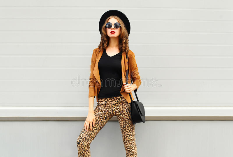 Fashion look, pretty woman wearing a retro elegant hat, sunglasses, brown jacket and black handbag over background stock images