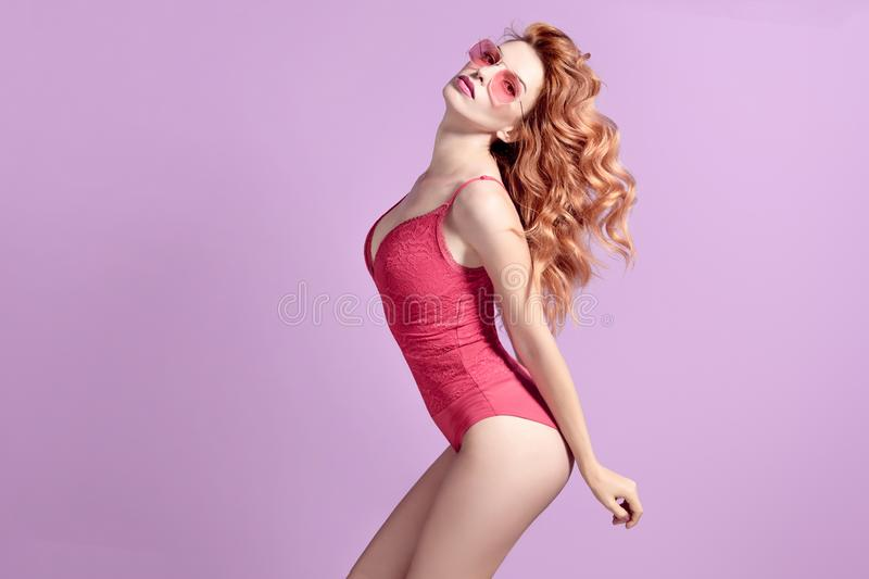 Fashion. Lovable Girl in bodysuit, Wavy Hairstyle. Fashion Lovable Redhead Girl in Pink Outfit with Trendy Wavy Hairstyle, Stylish Sunglasses. Young Gorgeous stock image