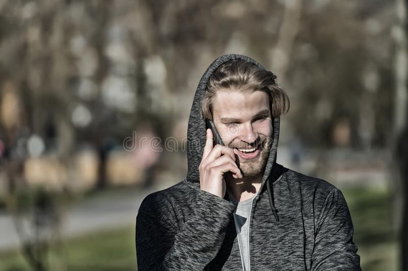 Fashion macho smiling with smartphone in casual sweatshirt. Happy guy in hood talk on mobile phone on sunny outdoor. Bearded man s royalty free stock images