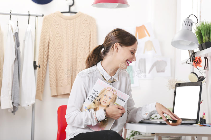 Fashion magazine editor in her office. Young fashion woman smiling stock image