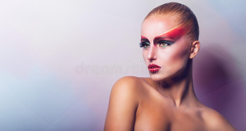 Fashion make-up. Beautiful woman with fashion make-up in the studio on a light background royalty free stock photography