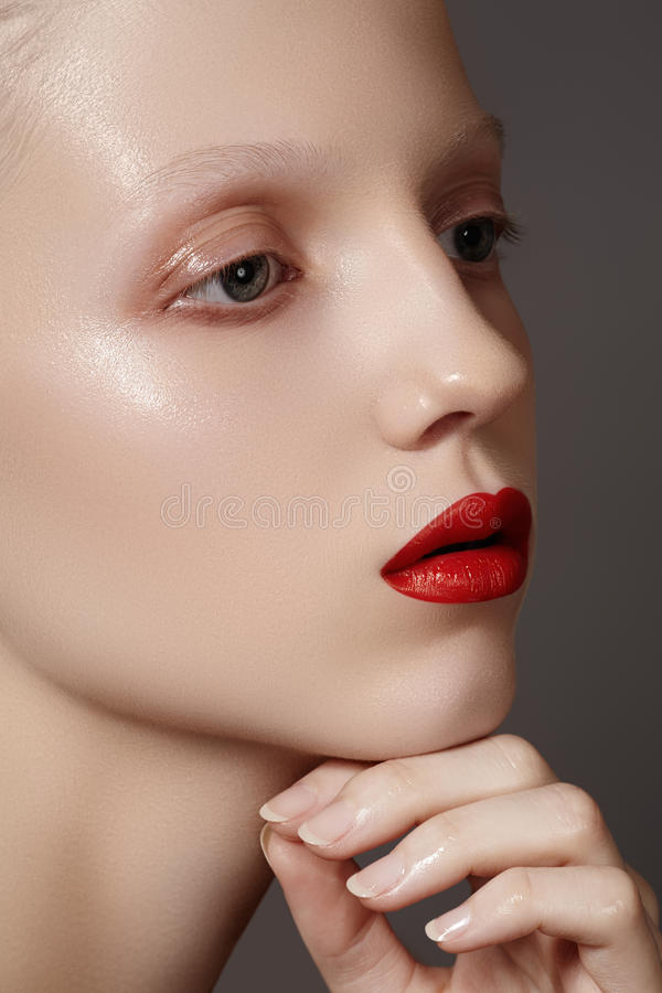 Fashion make-up & cosmetics. Glamour model face with bright red lips, clean shiny skin. Close-up portrait of caucasian young woman model with glamour red lips royalty free stock images