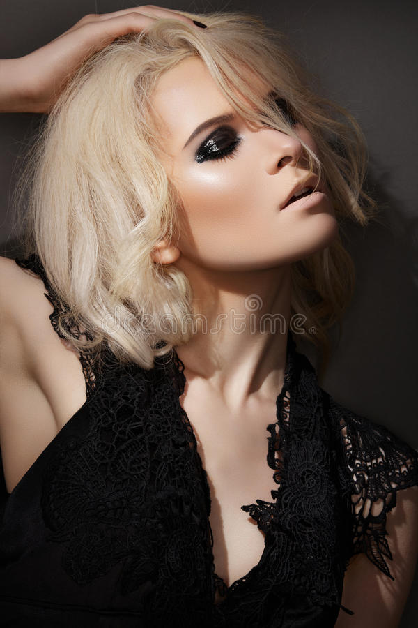 Fashion make-up. blond model in black dress. Evening or night rock fashion style. Blond woman model with dark evening wet gloss make-up in a fashionable black stock images