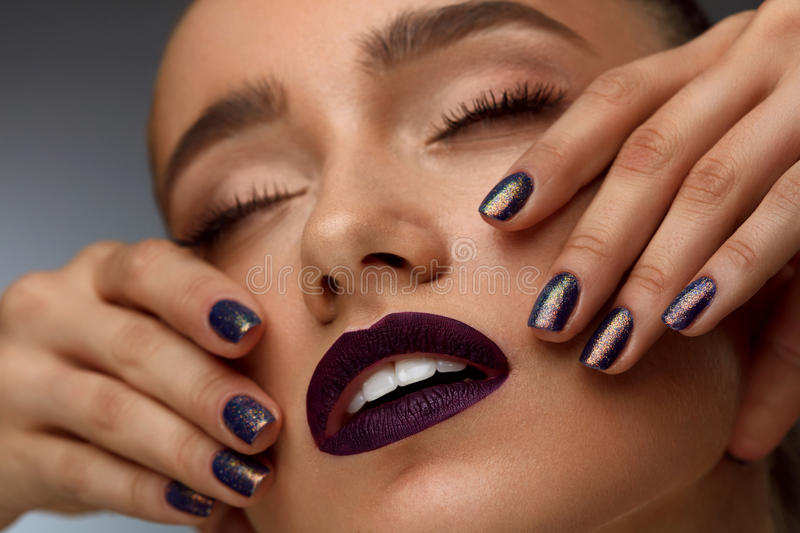 Fashion Makeup. Beautiful Woman With Dark Lips And Purple Nails royalty free stock photography