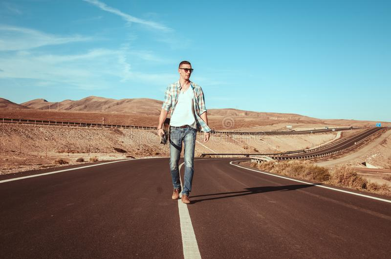 Fashion man alone walk on the road with guitar stock photos