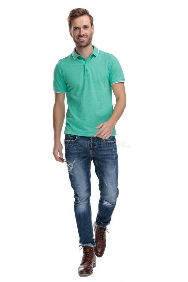 Fashion man in green polo shirt walking. On white background stock image