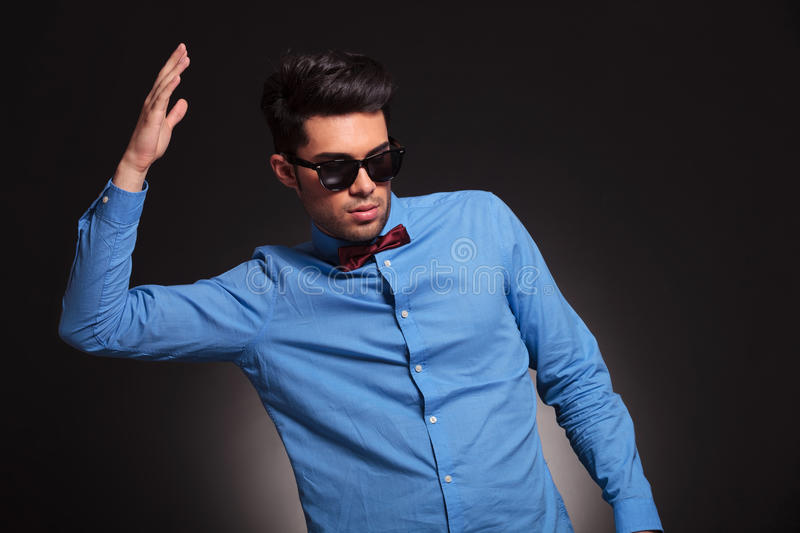Fashion man with hand inthe air. Fashion man in sunglasses and wearing bow tie with his hand in the air stock photo