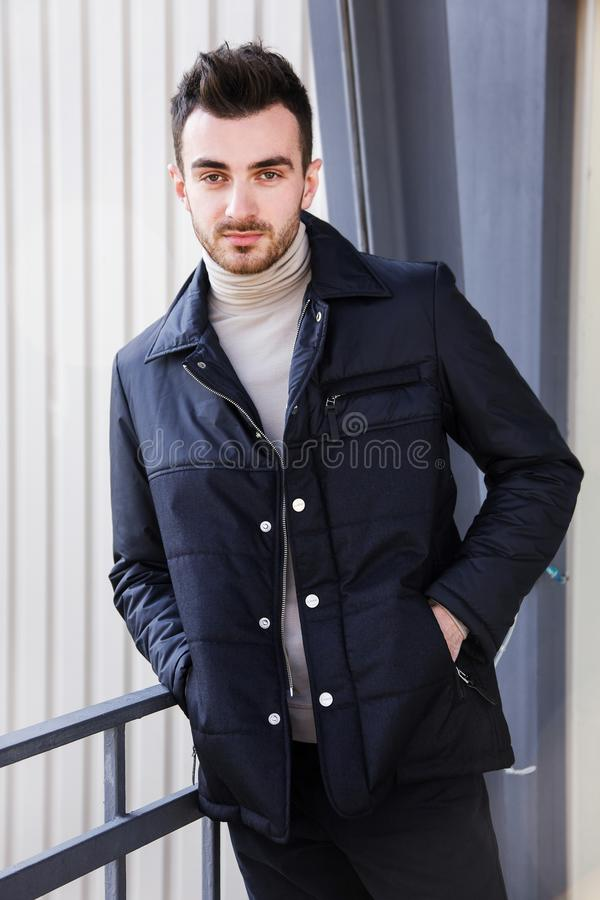 Man serious male model portrait blue jacket young guy gray background autumn winter black friday stock photography