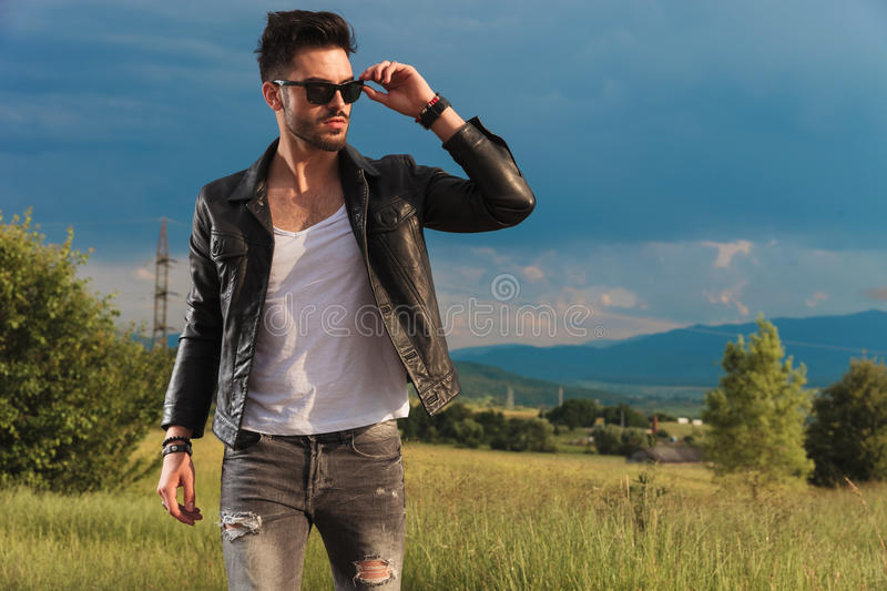 Fashion man in leather jacket putting on his sunglasses royalty free stock images