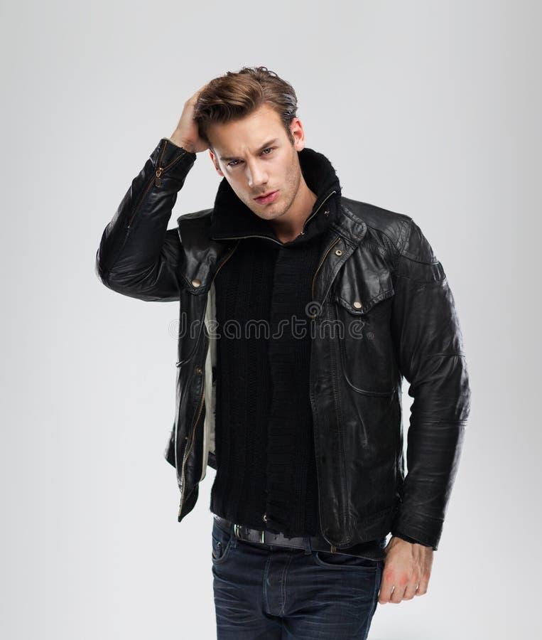 Fashion man, model leather jacket, gray background stock images