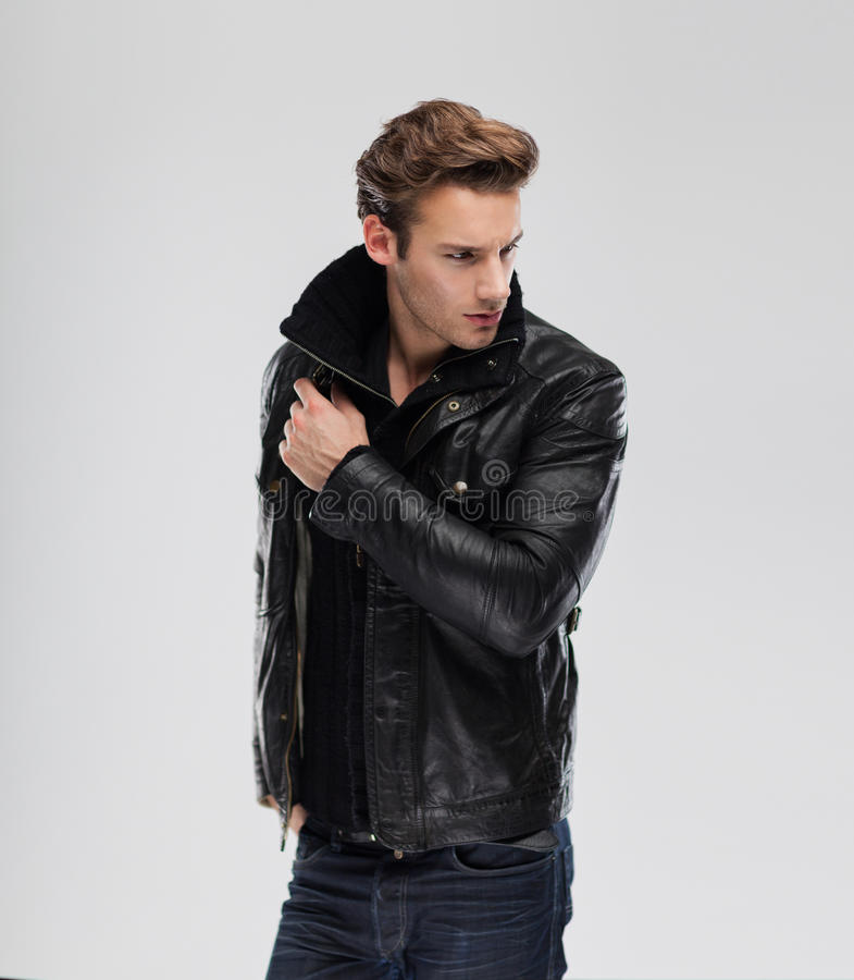 Fashion man, model leather jacket, gray background royalty free stock images