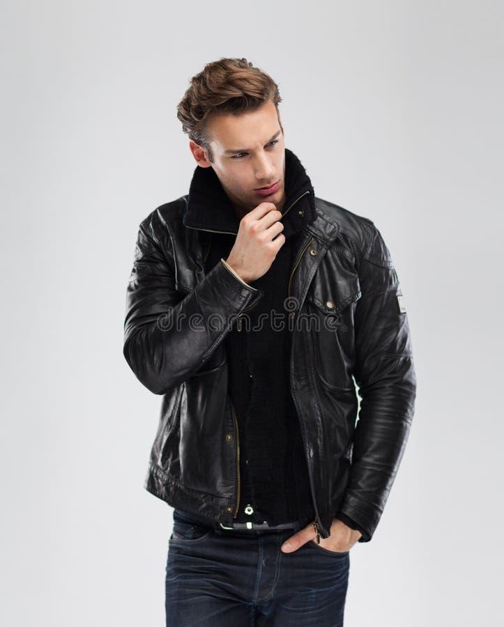 Fashion man, model leather jacket, gray background royalty free stock photography