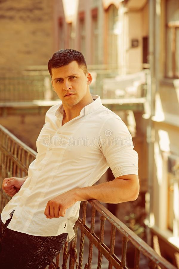Fashion man relax on house balcony. Fashion model in fashionable shirt and jeans.  royalty free stock images