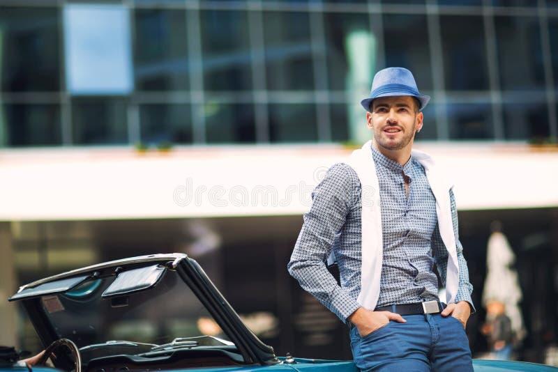 Fashion man standing near retro cabriolet car stock image