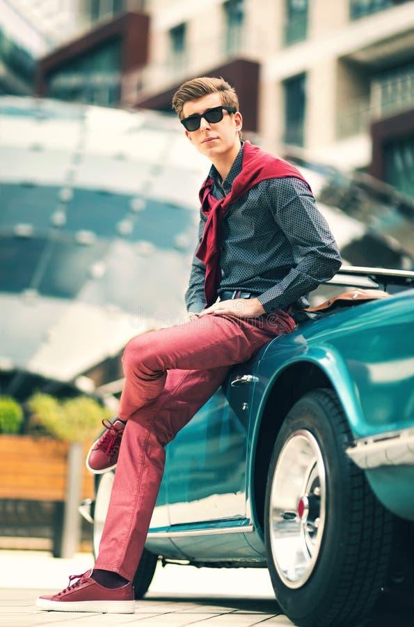 Fashion man standing near retro cabriolet car stock photo