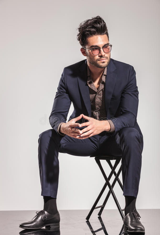 Fashion man in suit sitting and looks to side stock photos
