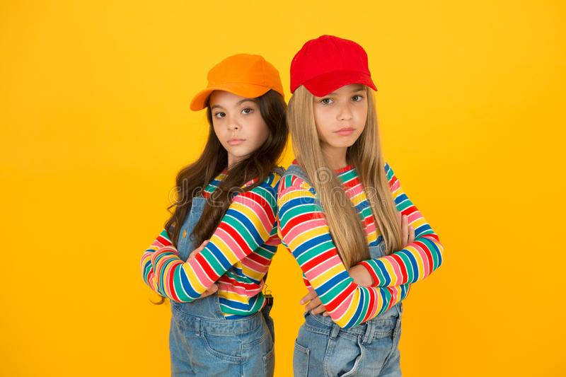 Fashion that matches their conscious style. Small girls in style keeping arms crossed on yellow background. Little royalty free stock image