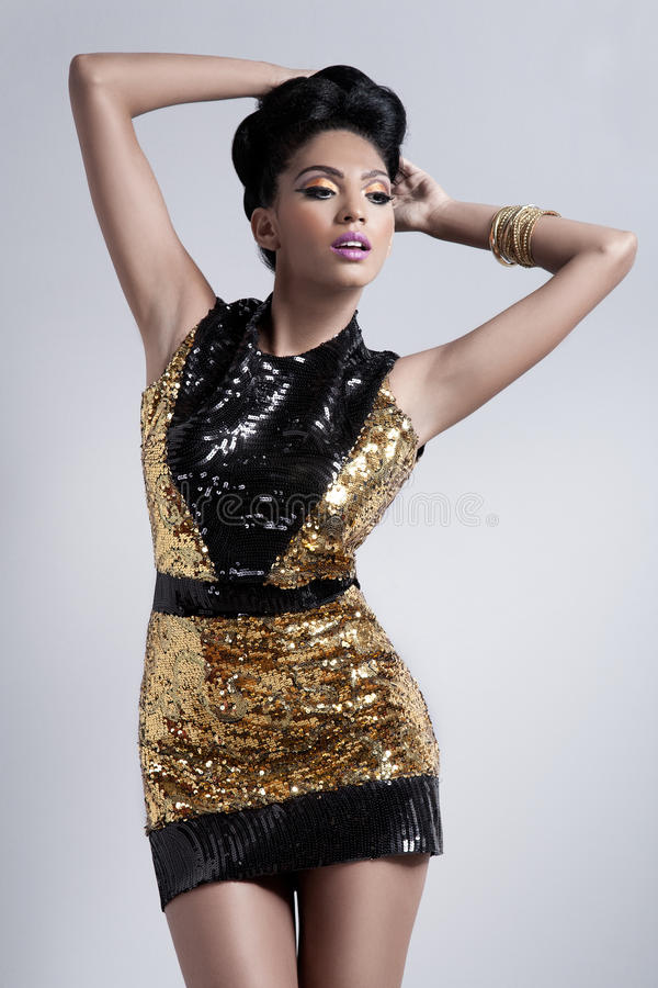 Fashion model. Glamorous shapely young fashion model wearing a gold mini dress royalty free stock images