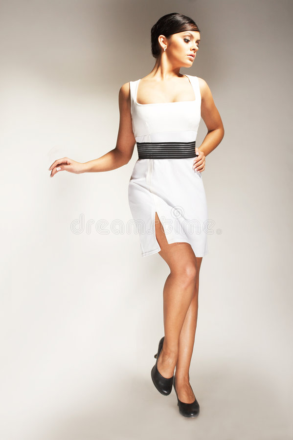 Fashion model. Posed on light background in white dress stock images