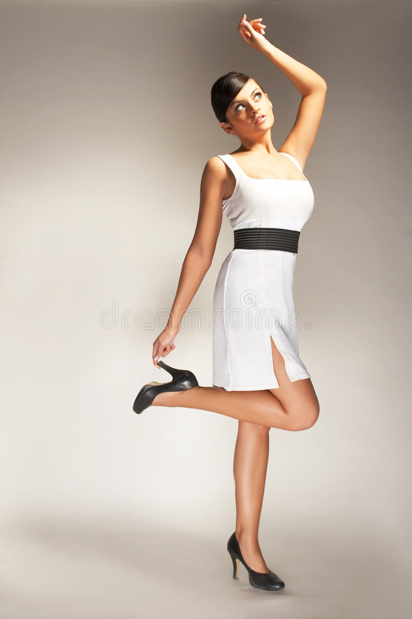 Fashion model. Posed on light background in white dress royalty free stock image