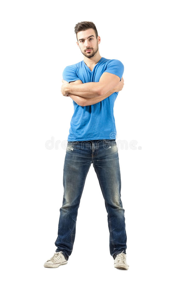 Fashion model with arms wrapped around looking at camera. Young fashion model with arms wrapped around himself looking at camera. Full body length isolated over royalty free stock images