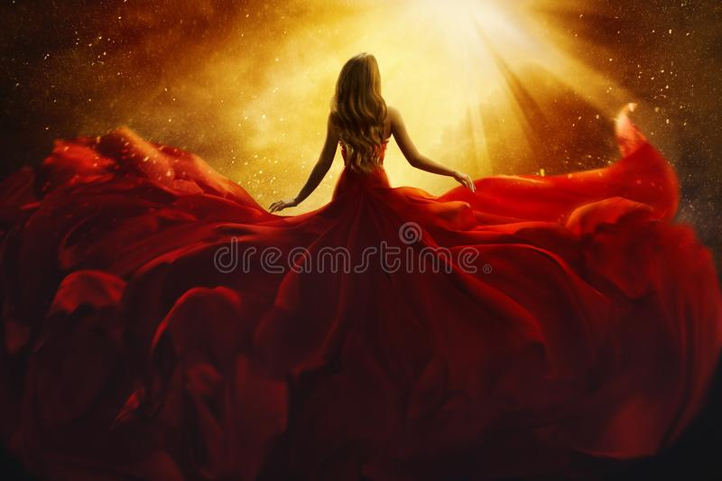 Fashion Model Back Side in Red Flying Dress, Woman Rear View. Gown Fabric Fly on Wind, Beautiful Girl Looking to Light stock image