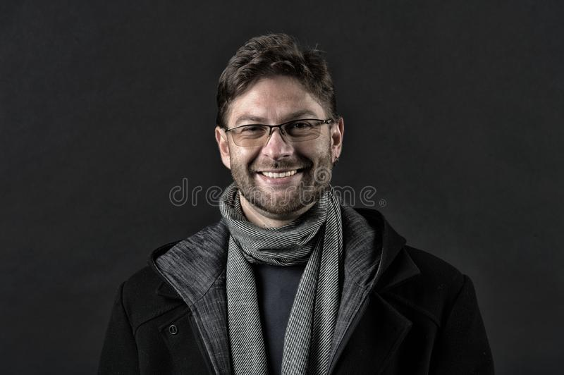 Fashion model with beard smile on dark background. Happy man in glasses on bearded face. Bearded man in scarf and coat stock photo