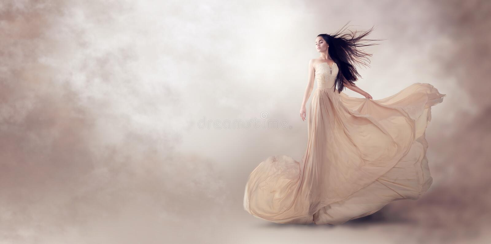 Fashion model in beautiful beige flowing chiffon dress royalty free stock photography