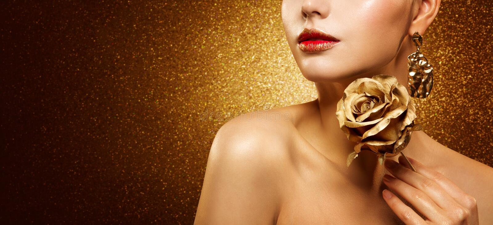 Fashion Model Beauty Make Up, Beautiful Woman hold Gold Flower Rose and Luxury Golden Makeup stock photo