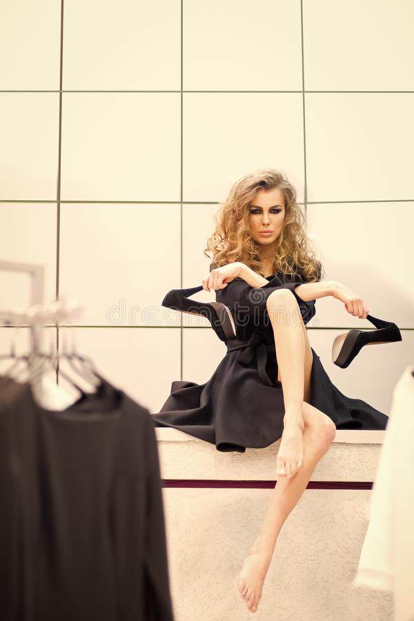 Fashion model with black high heel shoes in dressing room. Sensual woman with makeup face, long hair, beauty in shop. Fashion, style, vogue. Beauty, look, make stock photo
