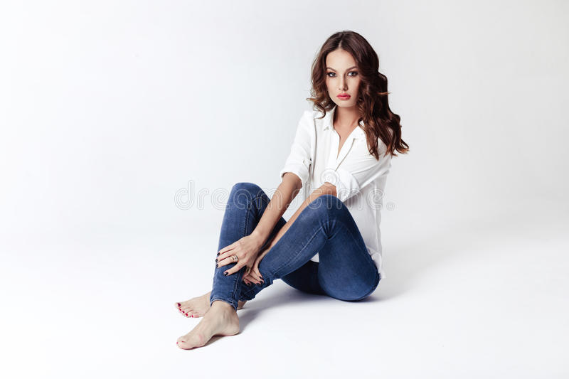 Fashion model in a blouse and jeans barefoot. Fashion model sitting on a floor in a blouse and jeans barefoot on a white background stock images