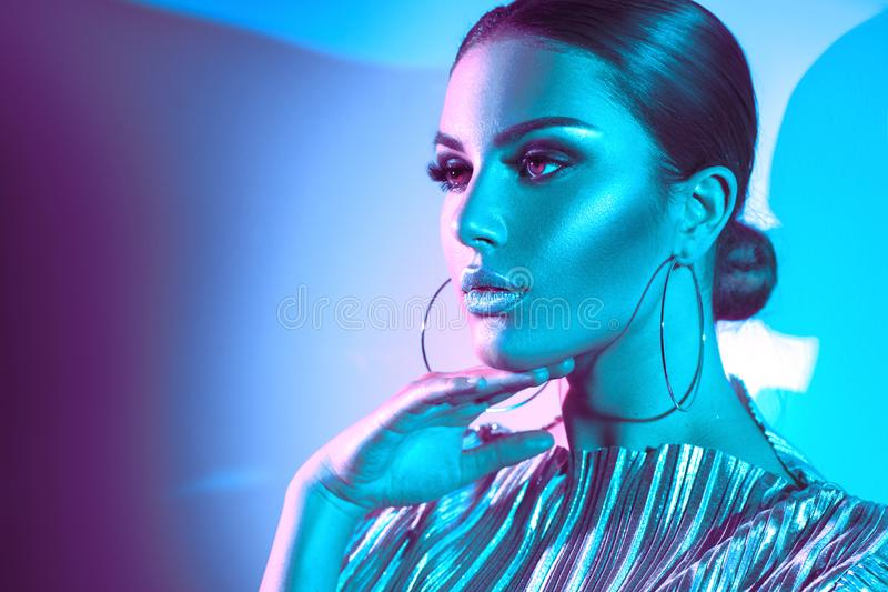 Fashion model brunette woman in colorful bright neon lights. Beautiful girl, trendy glowing makeup, metallic silver lips. Fashion model brunette woman in royalty free stock images