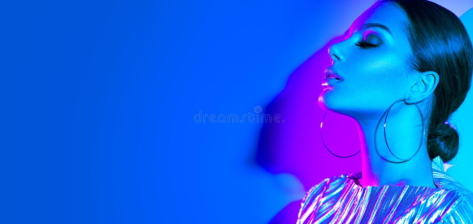 Fashion model brunette woman in colorful bright neon lights posing in studio. Beautiful girl, trendy glowing makeup stock images