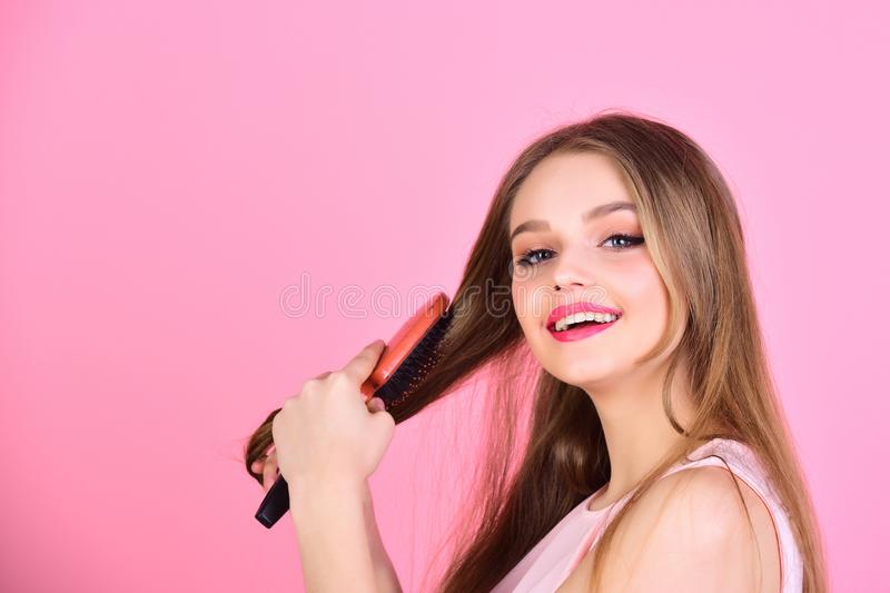 Fashion model brush her beautiful hair. Girl with hair brush on pink background. woman comb long straight hair stock image