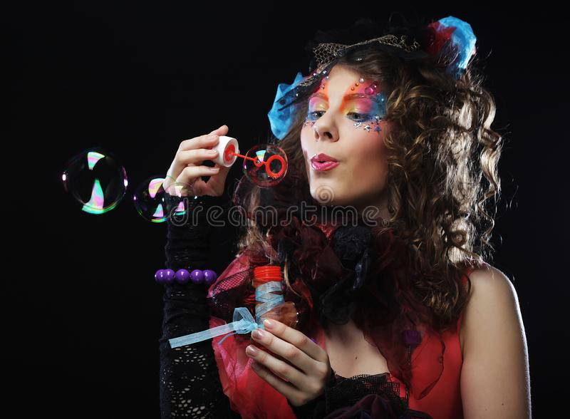 Fashion model with creative make-up blowing soap bubbles. Doll s stock photography
