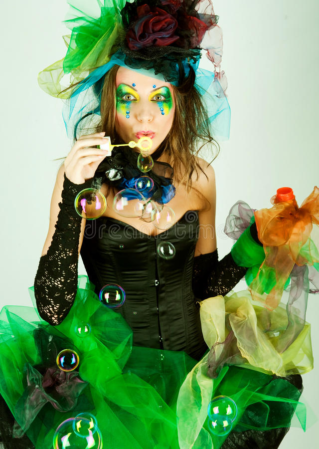 Fashion model with creative make-up blowing soap bubbles royalty free stock photos