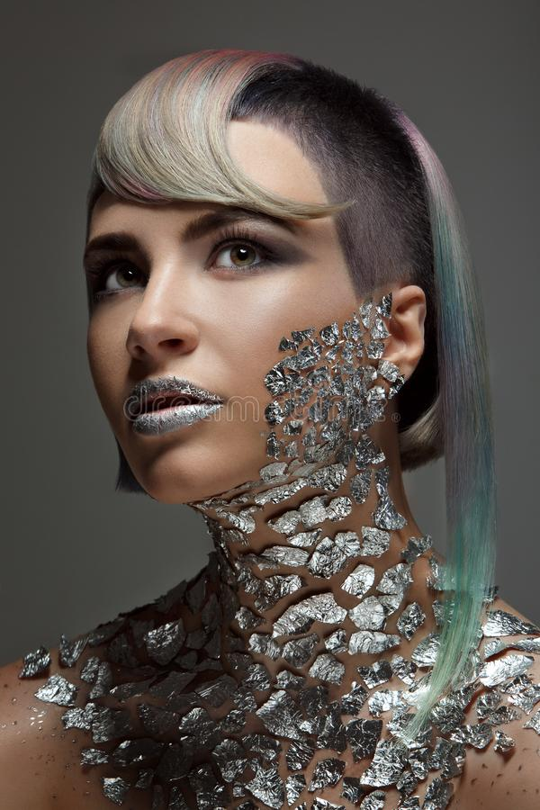 Fashion model with creative make-up and hairstyle. Foil, shiny shadows, glitter. Eyes, lips and colored hair coloring. Dark background royalty free stock images