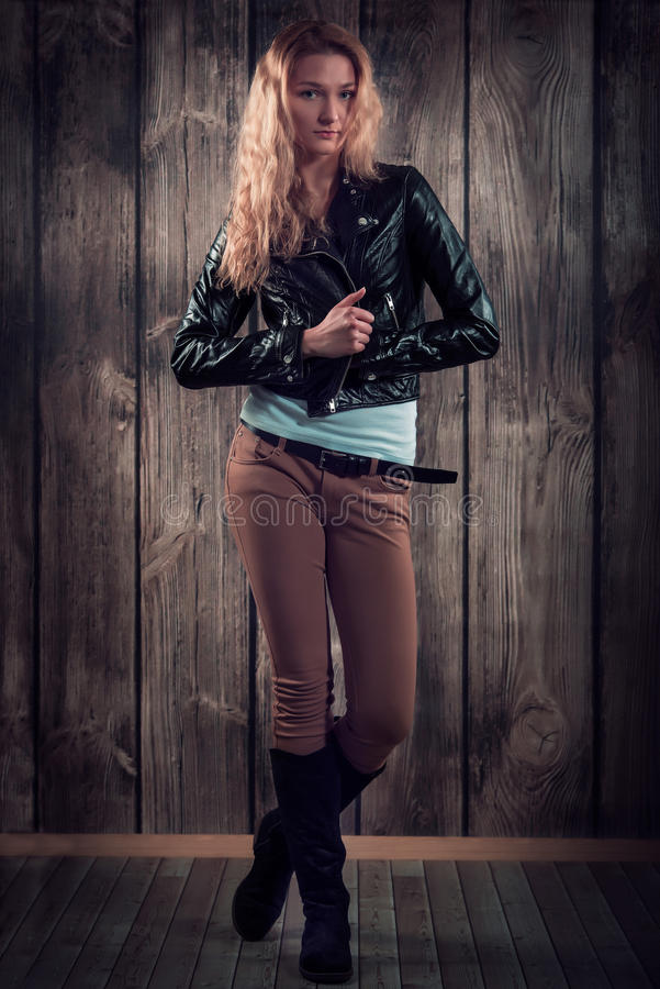 Fashion model with curly hair dressed in black jacket, denim pants and tall boots over wooden wall background. Lovely model with curly golden blond hair, happy stock photography