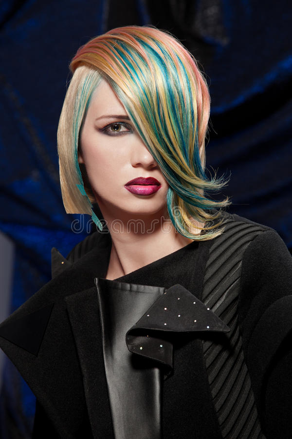 Fashion model with dyed hair. Beautiful blonde young woman with fancy coloured hair; portrait of a fashion model with dyed hair royalty free stock image