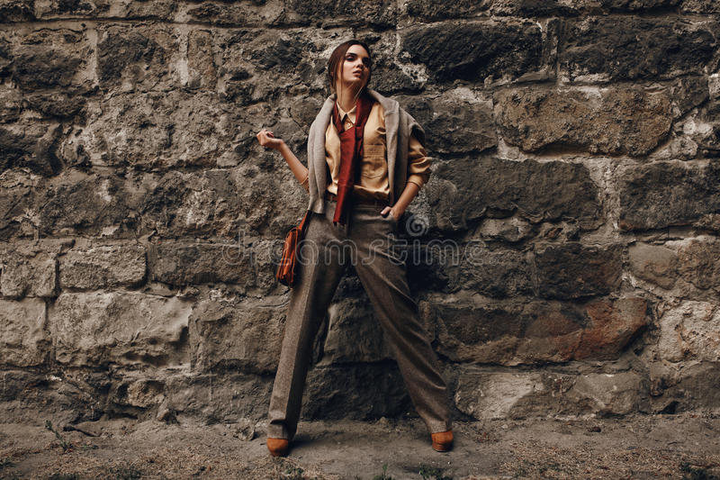 Fashion Model In Fashionable Clothes. Beautiful Woman Near Wall royalty free stock photography