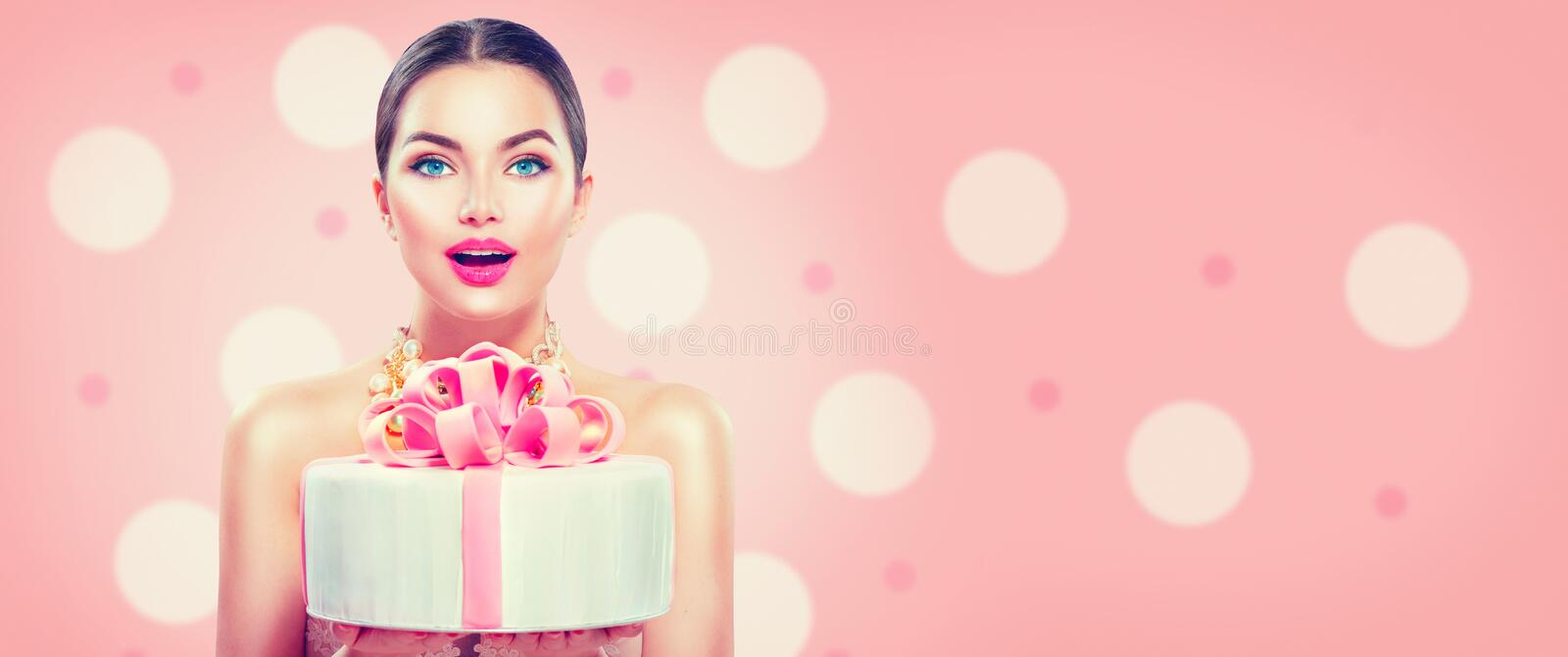 Fashion model girl holding beautiful party or birthday cake on pink background. Wide angle stock images